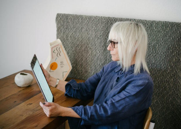 blond-old-woman-reading-book-on-tablet-3867185
